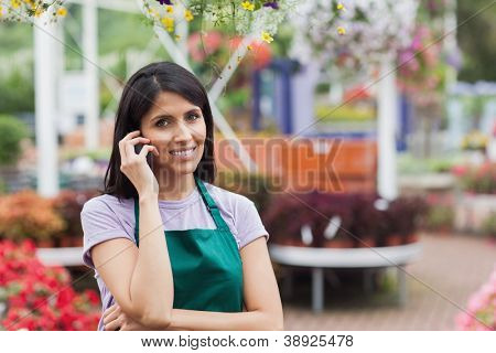 Woman working in garen center making a call and Smiling
