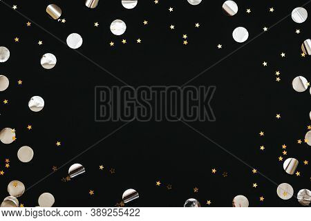 Gold And Silver Confetti On A Black Festive Background. In The Middle There Is Space For Text Or Cop