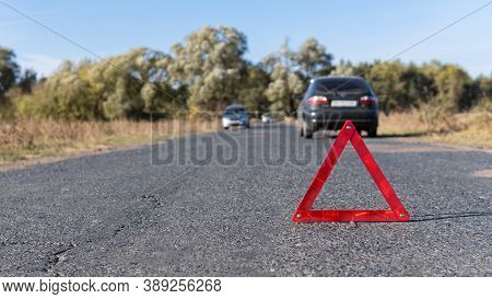 Emergency Triangle Stands On The Road In Front Of Cars On The Background. Breakdown Of The Car In Su