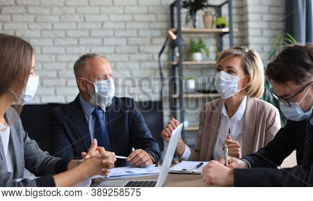 Business People Wearing Protective Face Masks While Holding A Presentation On A Meeting During Coron