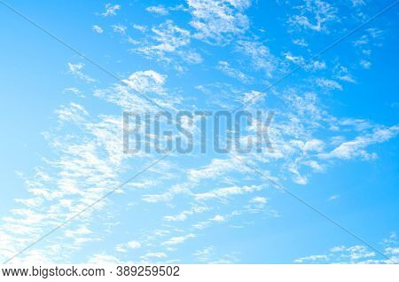 Blue sky background, white dramatic fluffy clouds lit by sunset light. Vast sky landscape scene, blue sky scene. Blue sky background, vast sky landscape, sky scene with dramatic clouds.