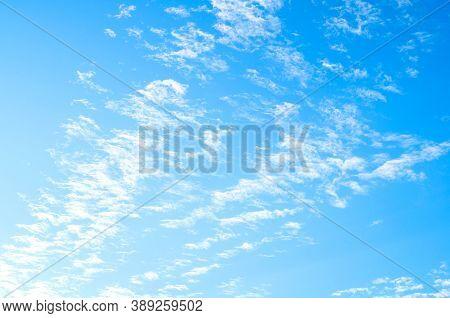 Blue sky background, white dramatic fluffy clouds lit by sunset light. Vast sky landscape scene, blue sky scene. Blue sky background, vast sky landscape, sky scene with dramatic clouds.