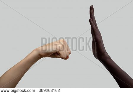Two Hands, Black And White. The White Fist Is Preparing To Strike The Black Palm.the Concept Of Inte