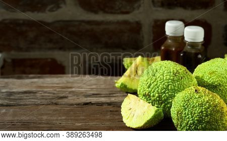 Fruit Of The Maclura Pomifera Tree Or Horse Apple On A Wooden Table. Sliced adam's Apple For Medic