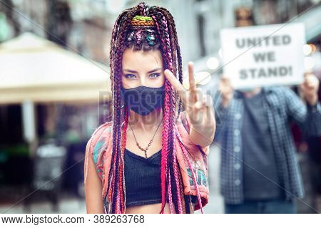Young Mixed Race Woman Wearing Face Mask Showing Peace Sign During Street Protest - Hipster Female P