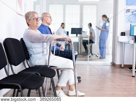 Senior Woman With Walking Frame In Hospital Waiting Room For Rehabilitation Treatment. Medical Staff