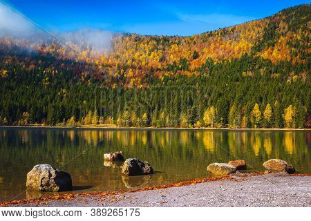Breathtaking Autumn Scenery With Colorful Deciduous Trees In The Forest And Majestic Volcanic Lake.
