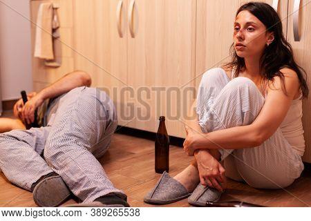 Helpless Beaten Woman Suffering Sitting On The Floor Near Drunk Man. Alcoholic Aggressive Husband Ab