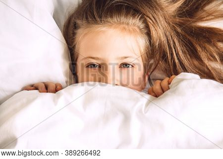 Child Hiding Under Duvet In Bed. Morning Routine. Indulge In The Bedroom In The Morning. Girl In Bed