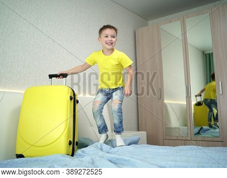 Happy Boy In The Hotel On The Bed Having Fun And Jumping With Happiness. Yellow Suitcase On The Bed