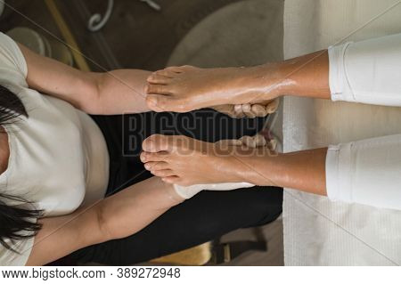 Enjoying A Feet Massage In A Spa. Close Up Of Feet. Woman Hands Giving A Foot Massage. Traditional S