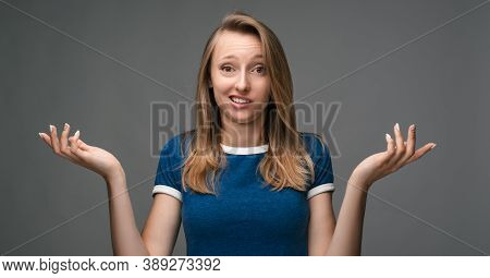 Studio Shot Of A Clueless Young Woman In A Blue Shirt, Shrugging Shoulders Looking At The Camera Bei