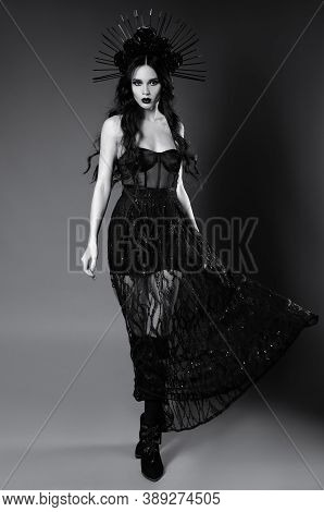 Halloween Theme: Attractive Young Witch In Black Dress And Headgear With Roses And Spikes. Dark Beau