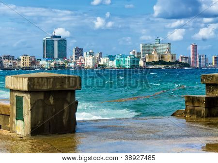 The skyline of Havana with a turbulent sea and El Malecon in the foreground