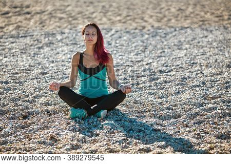 Female Meditating On Coastline. Concentrated Woman In Sportswear. Contemplation And Yoga Time. Healt