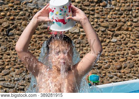 A Young Boy  Pours Cold Water Over His Head To Cool