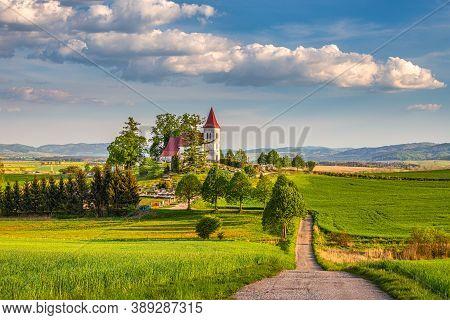 Rural Landscape With Road Toward A Church In The Abramova Village, Turiec Region, Slovakia, Europe.