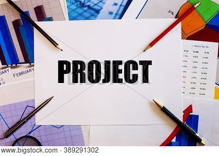 The Word Project Is Written On A White Background Near Colored Graphs, Pens And Pencils. Business Co