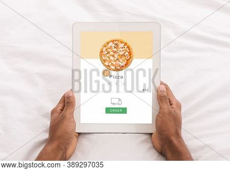 Fast And Convenient Ordering Of Food At Home In Bed. Hands Of African American Man Hold Tablet With