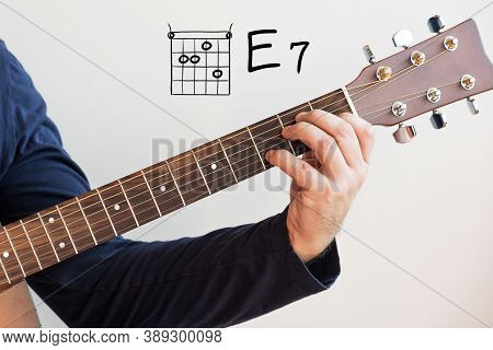 Learn Guitar - Man In A Dark Blue Shirt Playing Guitar Chords Displayed On Whiteboard, Chord E 7