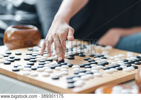 Player's Hand Put Stone On The Game Board - An Ancient Game Also Known As Baduk In Korean, Weiqi In