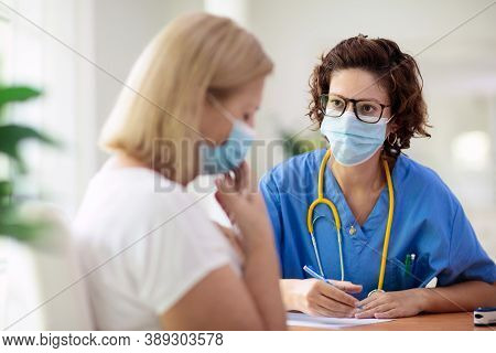 Doctor Examining Sick Patient In Face Mask. Ill Woman In Health Clinic For Test And Screening