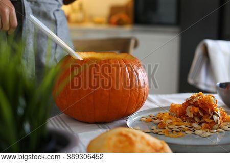 Woman Making Pumpkin Jack O'lantern At Table Indoors. Halloween Celebration