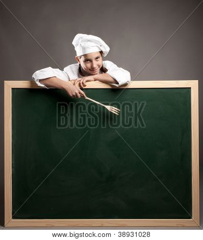 young chef holding green chalkboard