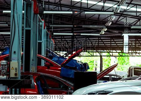 Auto Repair Shop. Suv Car Is Lift In Garage For Repair And Maintenance Service. Auto Service With Li