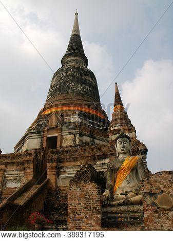Ayutthaya, Thailand, January 24, 2013: Stone Sculpture Of Buddha Next To A Stupa In Ayutthaya, Forme