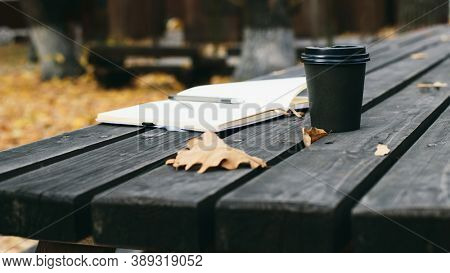 notepad and cup of coffee on an old wooden table, background image
