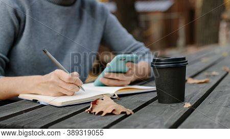 woman making notes while sitting on the veranda in autumn