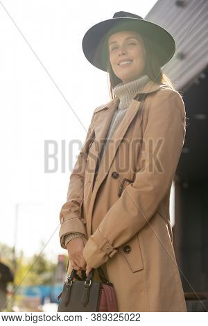 Young beautiful woman in black hat, beige trenchcoat and grey sweater looking at you with toothy smile while standing in front of camera