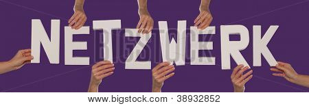 White alphabet lettering spelling NETZWERK in German held up over a purple studio background by outstreched female hands