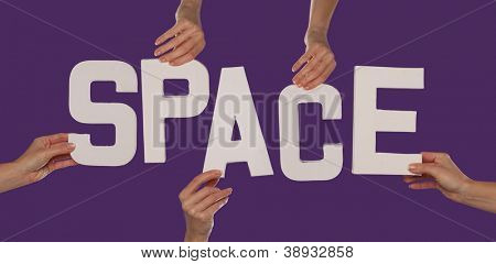 White alphabet lettering spelling SPACE held up over a purple studio background by outstreched female hands