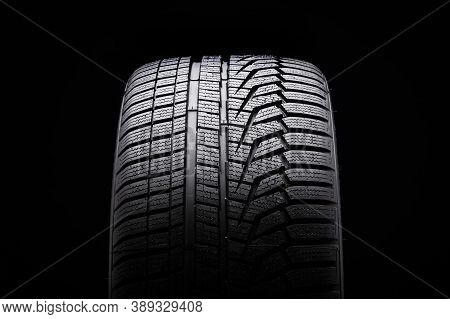 Winter Tire Front View. Asymmetric Tread Pattern. Re-inflating Tires For The Season. Close-up Black