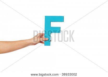 Female hand holding up the uppercase capital letter F isolated against a white background conceptual of the alphabet, writing, literature and typeface