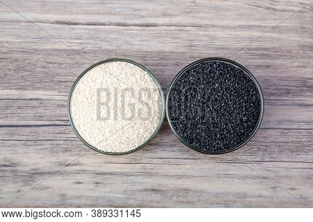 Black And White Sesame In Bowl On Wood Table Background. White Sesame And Black Sesame Seed In Bowls
