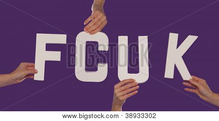 White alphabet lettering spelling FCUK held up over a purple studio background by outstreched female hands