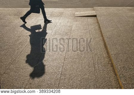 Silhouette Of A Girl On The Background Of A City Street. A Large Shadow Of A Woman Walking With A Ba