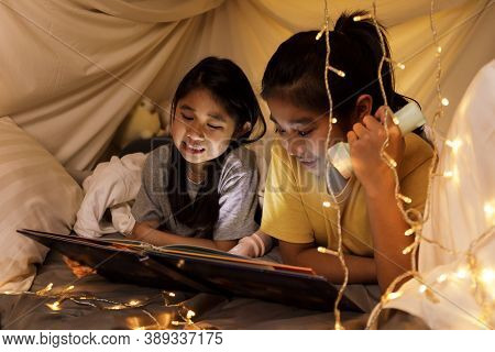 Family Concept. Elder Sister And Sister Reading Book With Flashlight Together In Children Tent Befor