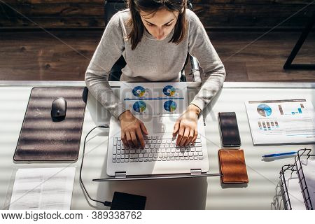 Woman Works In Office With Laptop At Worktable.