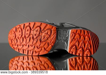 red sole of trekking sneaker, gray background