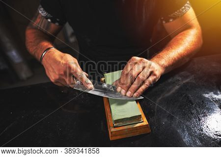 Mans Hands Sharpening Knife Withwhetstone, Close Up Shot