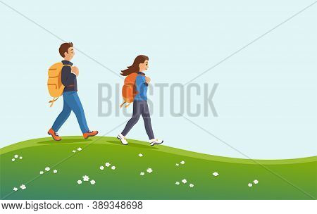 Man And Woman With Backpacks In Nature. They Walk With A Smile On The Green Grass. Hiking And Active