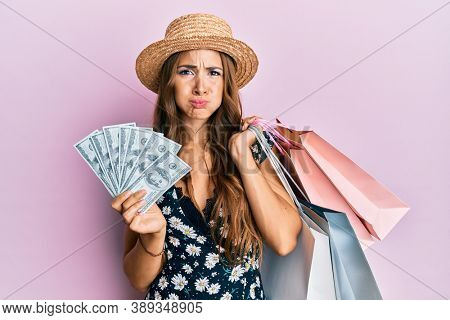 Young brunette woman holding shopping bags and dollars puffing cheeks with funny face. mouth inflated with air, catching air.