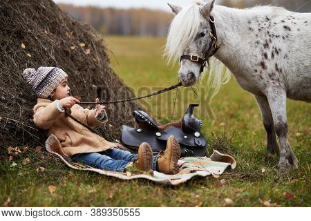 Horizontal shot of little girl wearing warm coat having rest with her little pony on hayfield