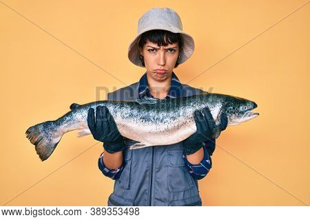 Beautiful brunettte fisher woman showing raw salmon depressed and worry for distress, crying angry and afraid. sad expression.
