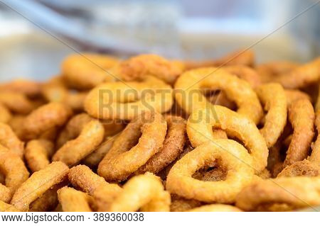 Large Group Of Freshly Fried Calamari And Onion Rings On Display For Sale At A Street Food Festival