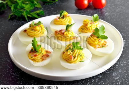 Deviled Stuffed Eggs With Egg Yolk, Bacon, Mustard And Parsley On Dark Stone Background, Close Up Vi